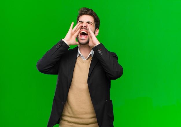 Junger geschäftsmann, der glücklich, aufgeregt und positiv sich fühlt, einen großen ruf heraus mit den händen nahe bei dem mund gebend und rufen auf grün aus