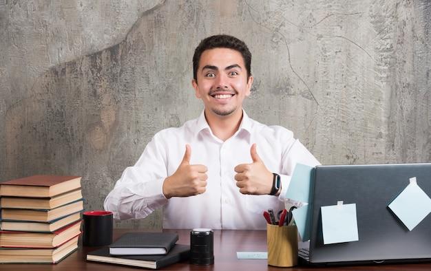 Junger geschäftsmann, der glücklich daumen oben im büro zeigt.
