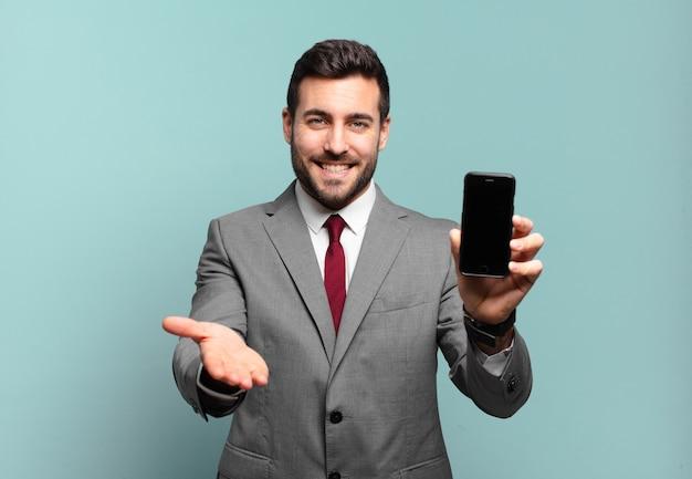 Junger geschäftsmann, der glücklich mit freundlichem, selbstbewusstem, positivem blick lächelt, ein objekt oder konzept anbietet und zeigt und seinen telefonbildschirm zeigt