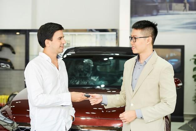 Junger geschäftsmann, der im autoausstellungsraum steht und einen schlüssel vom neuen auto vom asiatischen verkäufer erhält