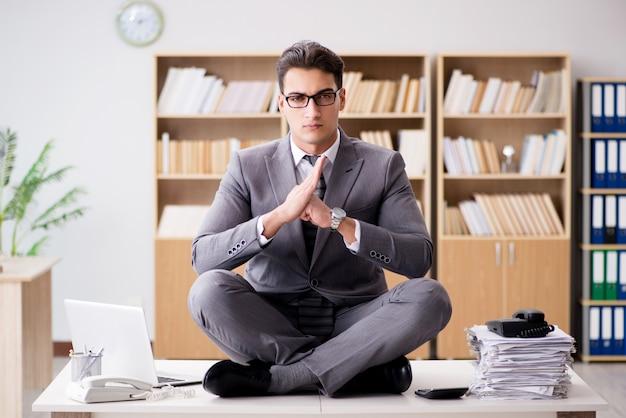 Junger geschäftsmann, der im büro meditiert