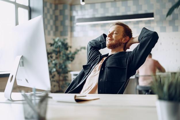 Junger geschäftsmann, der im büro mit händen hinter seinem kopf sitzt, der mit der geleisteten arbeit zufrieden ist