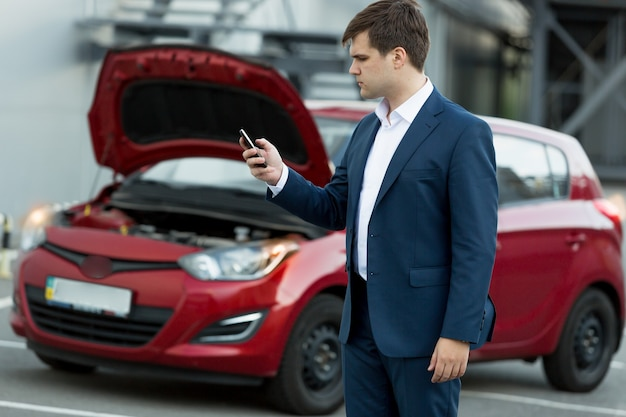 Junger geschäftsmann, der im handy sucht, wie man auto repariert?