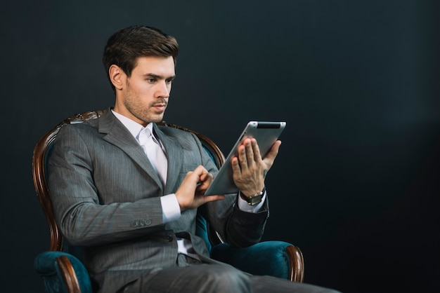 Junger geschäftsmann, der im lehnsessel unter verwendung der digitalen tablette gegen dunklen hintergrund sitzt
