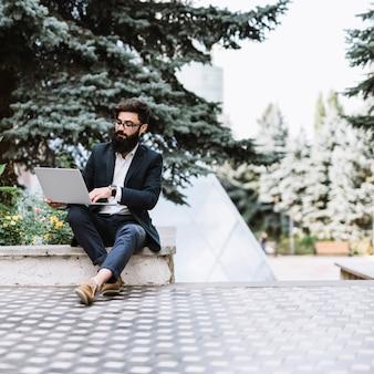 Junger geschäftsmann, der im park unter verwendung des laptops sitzt