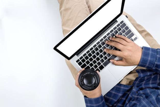 Junger geschäftsmann, der in der hand an der laptop-computer mit heißem kaffee arbeitet