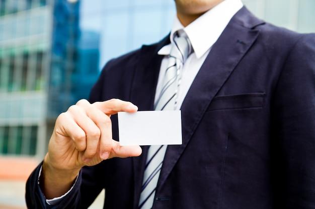 Junger geschäftsmann, der in der hand besuchskarte hält und in der front des bürogebäudes steht