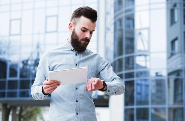 Junger geschäftsmann, der in der hand die digitale tablette überprüft zeit hält