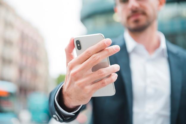 Junger geschäftsmann, der in der hand smartphone hält