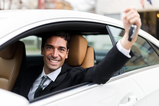 Junger geschäftsmann, der in seinem neuwagen zeigt autoschlüssel lächelt