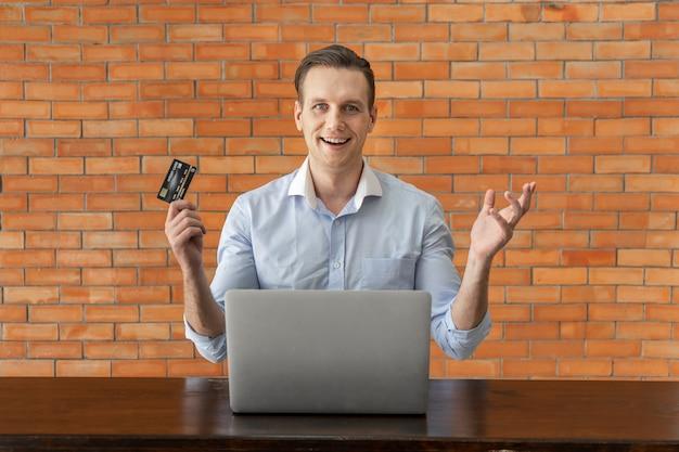 Junger geschäftsmann, der kreditkarte hält und laptop für das einkaufen online im kaffeehaus verwendet