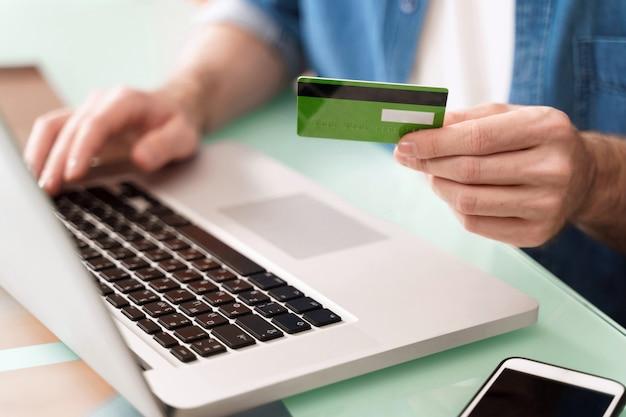 Junger geschäftsmann, der kreditkarte hält und laptop für e-commerce verwendet
