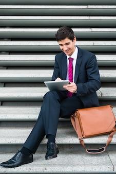 Junger geschäftsmann, der lächelt, während er einen tablet pc für online-kommunikation oder datenspeicherung im freien verwendet