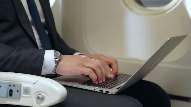 Junger geschäftsmann, der laptop im flugzeug verwendet