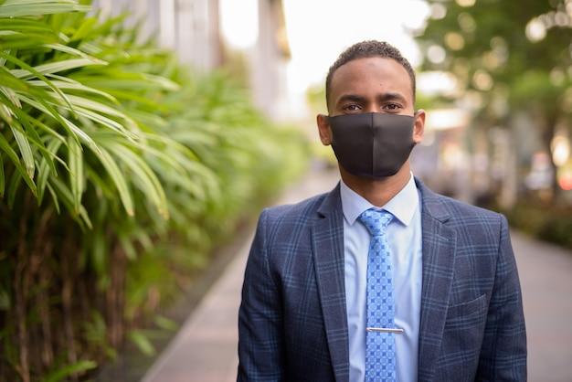 Junger geschäftsmann, der maske zum schutz vor ausbruch des koronavirus im freien trägt