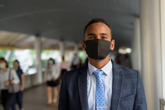 Junger geschäftsmann, der maske zum schutz vor dem ausbruch des koronavirus am steg mit leuten trägt, die gehen