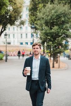 Junger geschäftsmann, der mit digitaler tablette und kaffeetasse auf stadtstraße geht