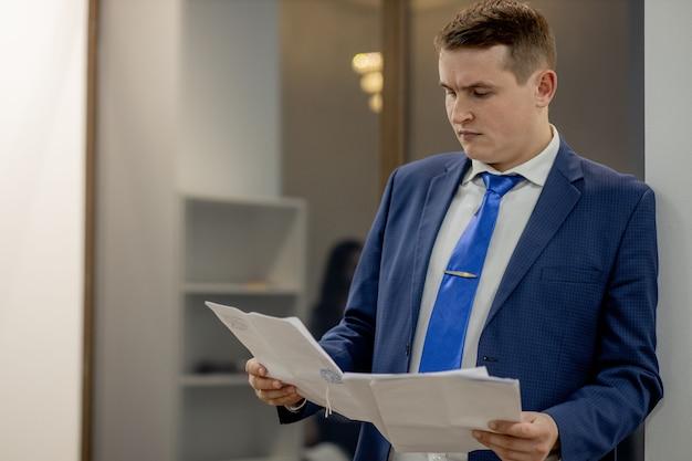 Junger geschäftsmann, der mit dokumenten arbeitet, die durch papiere im ordner schauen, am schreibtisch sitzen.
