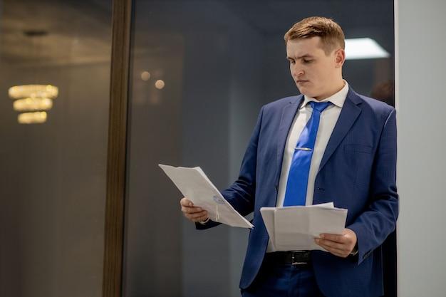 Junger geschäftsmann, der mit dokumenten arbeitet, die durch papiere im ordner schauen