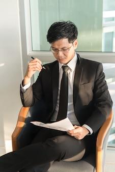 Junger geschäftsmann, der mit druck in einem büro arbeitet