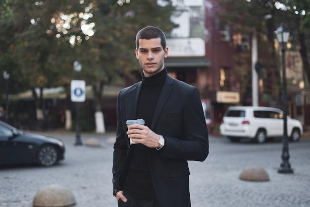 Junger geschäftsmann, der mit kaffee zur arbeit geht