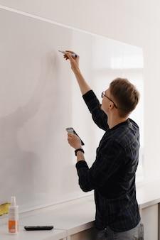 Junger geschäftsmann, der mit kollegen über whiteboard im büro diskutiert