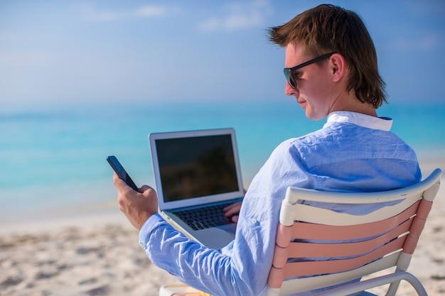 Junger geschäftsmann, der mit laptop auf tropischem strand arbeitet