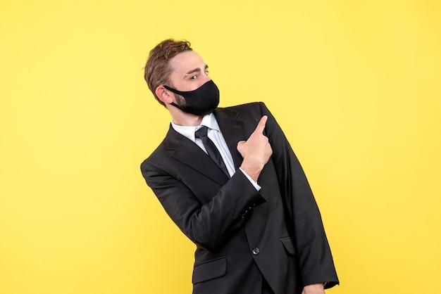 Junger geschäftsmann, der mit seinem finger linke seite mit medizinischer maske auf gelb zeigt