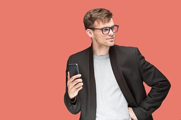 Junger geschäftsmann, der mobiltelefon hält