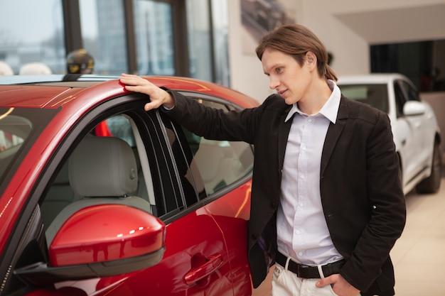 Junger geschäftsmann, der modernes automobil auf verkauf am autohaus untersucht, raum kopiert