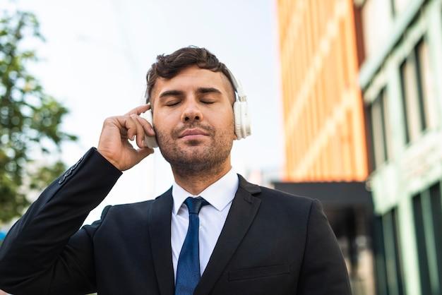 Junger geschäftsmann, der musik hört