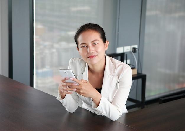 Junger geschäftsmann der nahaufnahme, der am stuhl auf arbeitsplatz im büro unter verwendung des smartphone sitzt