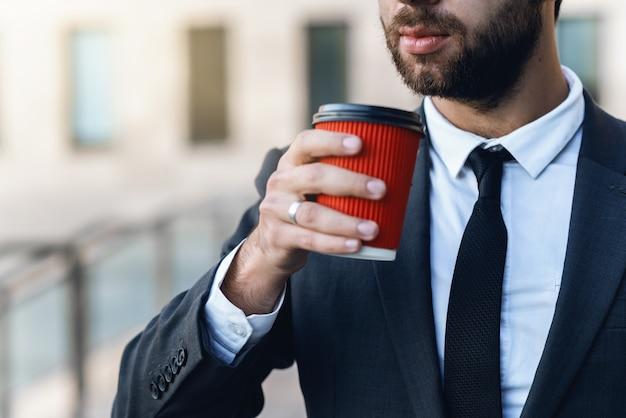 Junger geschäftsmann der nahaufnahme in der klage hält in der hand einen roten papiertasse kaffee