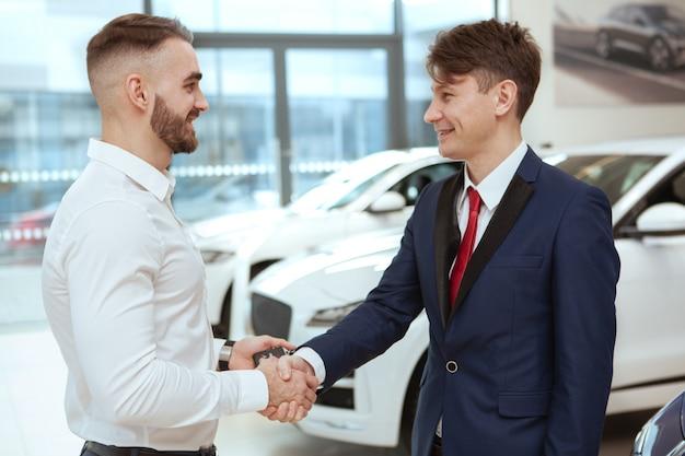 Junger geschäftsmann, der neues automobil kauft