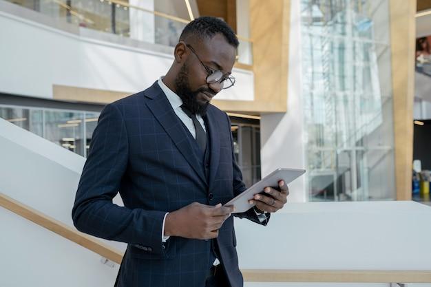 Junger geschäftsmann, der online-nachrichten auf dem tablet-display durchsieht