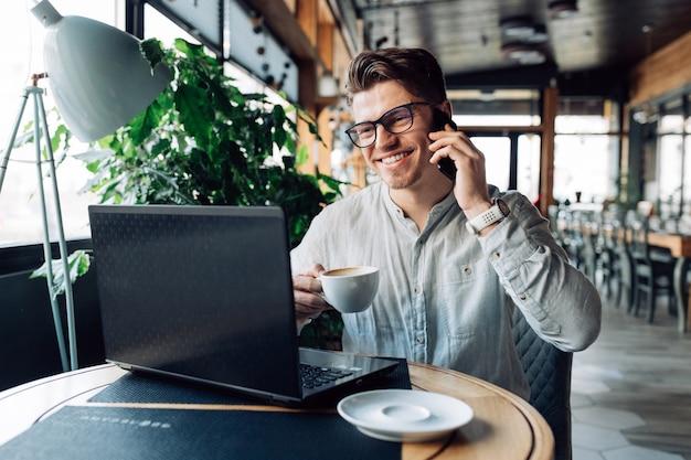 Junger geschäftsmann der perspektive in den brillen, einen tasse kaffee halten und sprechen am telefon