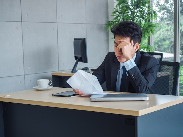 Junger geschäftsmann, der schlechte nachrichten mit entlassungsschreiben erhält, müde, gestresst und traurig sitzt mit geistesabwesend auf seinem schreibtisch im büro.
