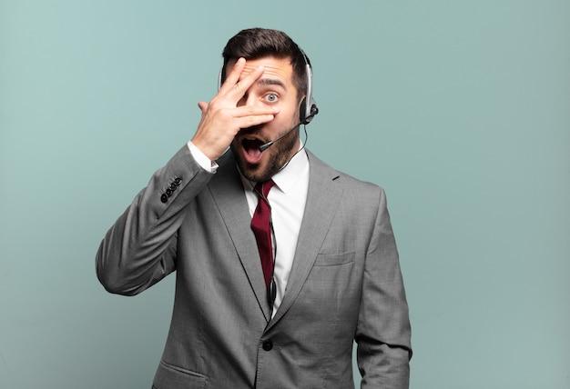 Junger geschäftsmann, der schockiert, ängstlich oder verängstigt schaut, gesicht mit hand bedeckt und zwischen fingern telemarketing-konzept späht