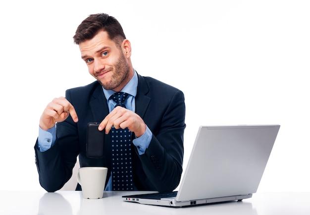 Junger geschäftsmann, der sein telefon in kaffeetasse setzt