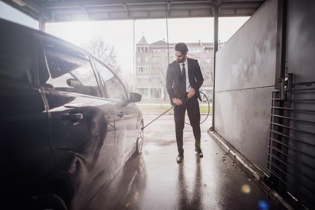 Junger geschäftsmann, der sein teures auto in der autowäsche wäscht.