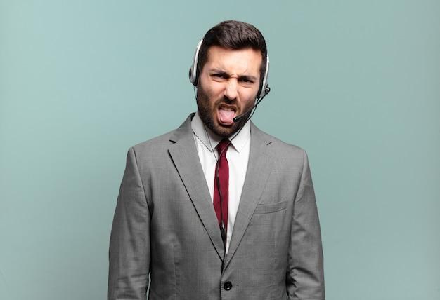 Junger geschäftsmann, der sich angewidert und irritiert fühlt, die zunge herausstreckt und etwas böses und ekliges telemarketing-konzept nicht mag