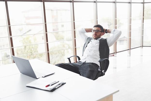 Junger geschäftsmann, der sich ausruht, während er im reinraum auf einem stuhl sitzt und auf den laptop schaut?