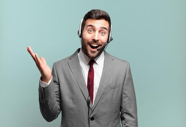 Junger geschäftsmann, der sich glücklich, überrascht und fröhlich fühlt, mit positiver einstellung lächelt und eine lösung oder ein ideen-telemarketing-konzept realisiert