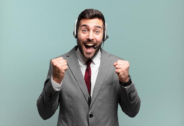 Junger geschäftsmann, der sich schockiert, aufgeregt und glücklich fühlt, lacht und erfolg feiert und wow sagt! telemarketing-konzept
