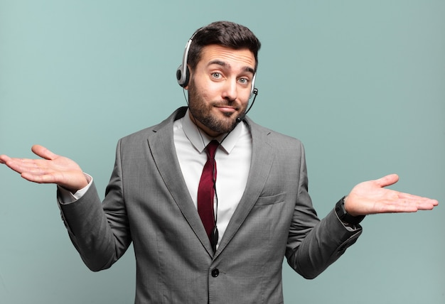 Junger geschäftsmann, der sich verwirrt und verwirrt fühlt, zweifel, gewichtung oder auswahl verschiedener optionen mit telemarketing-konzept des lustigen ausdrucks