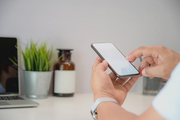 Junger geschäftsmann, der smartphone an einem arbeitsplatz hält