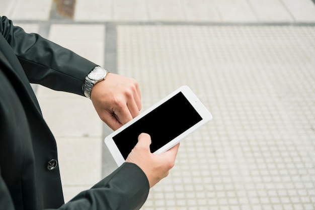 Junger geschäftsmann, der smartphone überprüft die zeit auf armbanduhr hält