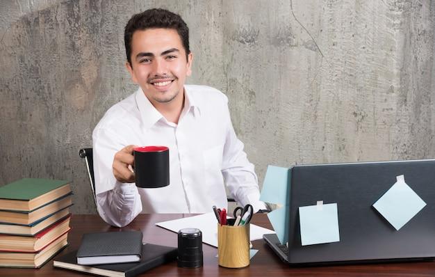 Junger geschäftsmann, der tasse tee am schreibtisch hält.