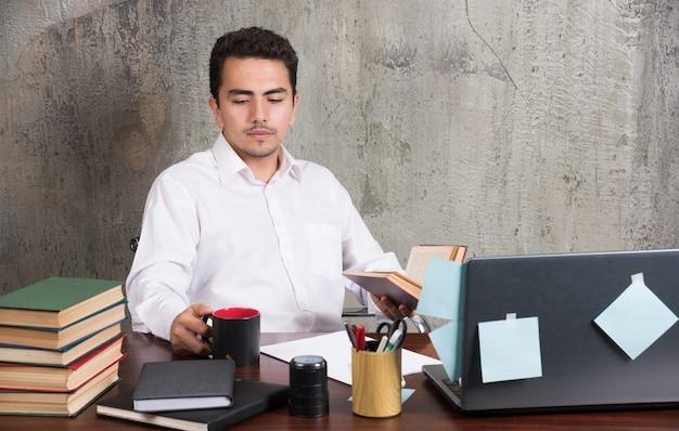 Junger geschäftsmann, der tasse tee am schreibtisch sieht.
