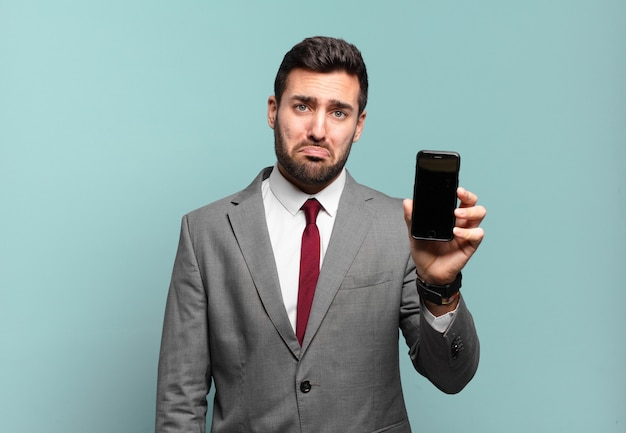 Junger geschäftsmann, der traurig und weinerlich mit einem unglücklichen blick fühlt, mit einer negativen und frustrierten haltung weint und seinen telefonbildschirm zeigt